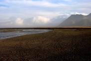 Über dem Schwemmfächer der Jekulsa á Leoni presst die Sturmfront Wolkenberge gegen die Steilküste